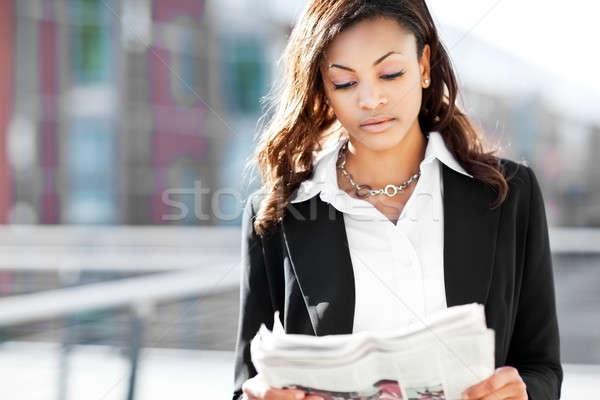 Stock photo: Black businesswoman reading newspaper
