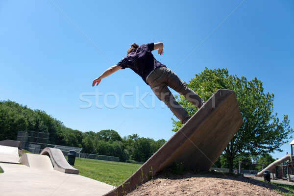 Skateboarder Riding Up a Concrete Skate Ramp Stock photo © ArenaCreative