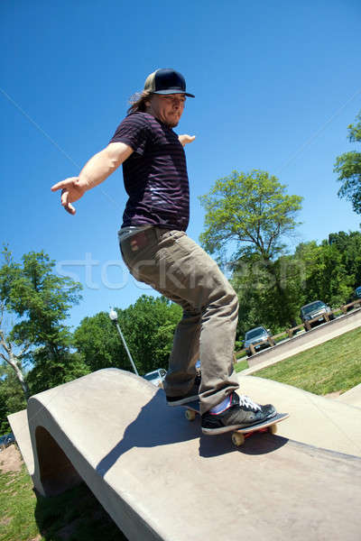 Skateboarder Rail Grinding at a Concrete Skate Park Stock photo © ArenaCreative