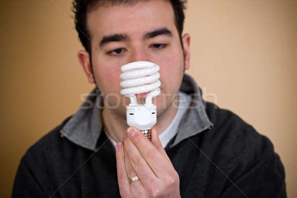 Compact fluorescent ampoule jeune homme énergie Photo stock © ArenaCreative