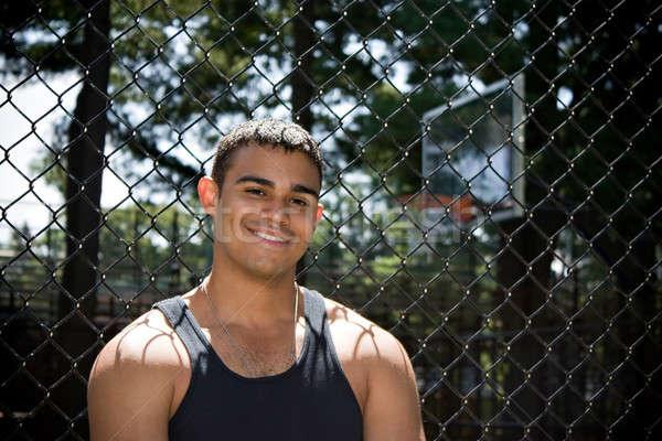 Uśmiechnięty młody człowiek stwarzające na zewnątrz boisko do koszykówki Zdjęcia stock © ArenaCreative