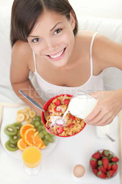 Woman eating breakfast in bed Stock photo © Ariwasabi