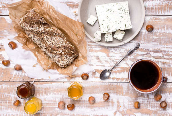 Morning tea Bread with seeds huzelnuts and cheese on board Stock photo © Arsgera