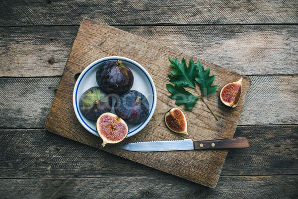 Figs and knife on chopping board and wooden table Stock photo © Arsgera