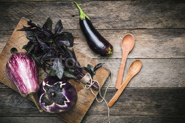 Aubergines with basil and spoons on wooden table Stock photo © Arsgera