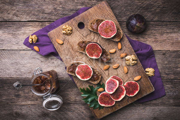Sliced figs on bread with jam and nuts in rustic style Stock photo © Arsgera