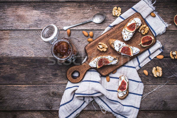 Bruschetta with figs and nuts on board in rustic style Stock photo © Arsgera
