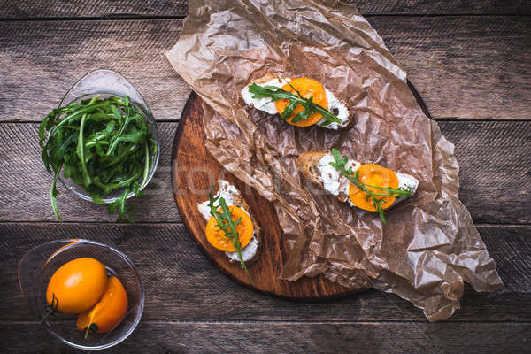 Bruschetta with tomatoes and arugula on board in rustic style Stock photo © Arsgera