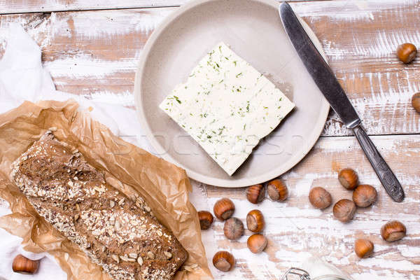 cheese with dill and bread huzelnuts on wooden board Stock photo © Arsgera