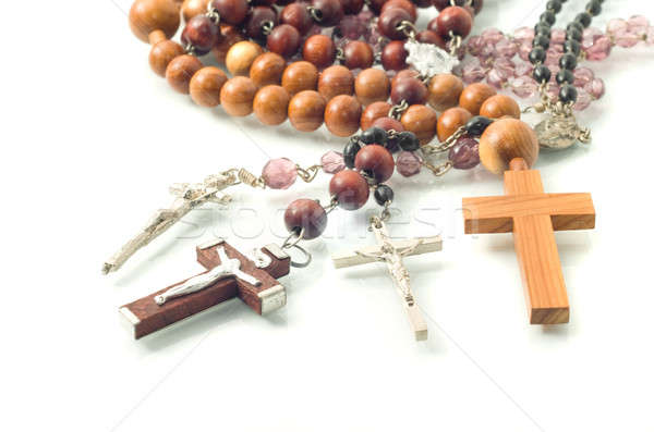 Rosary beads over white with focus on crosses  Stock photo © Arsgera