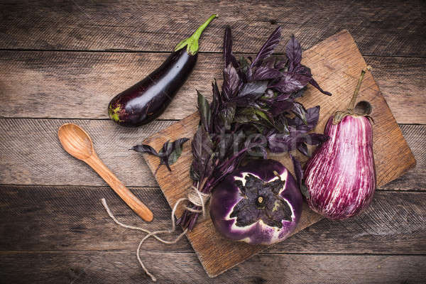 Aubergines, basil and spoon on chopping board and wooden table Stock photo © Arsgera