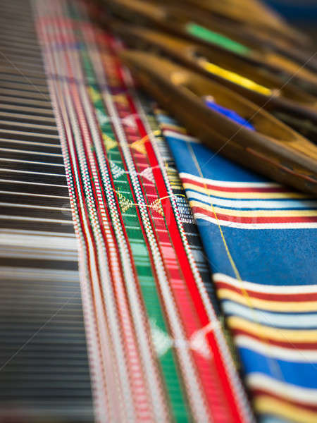 Weaving shuttles and colorful textile with pattern Stock photo © Arsgera
