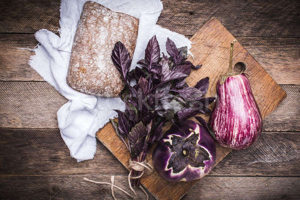 Aubergines, basil and bread on chopping board and wood Stock photo © Arsgera