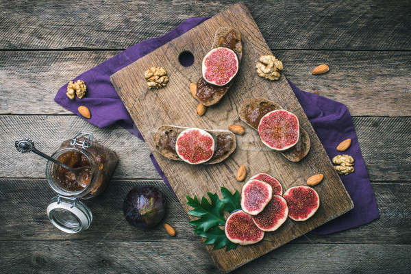 Cut figs, nuts and bread with jam on wooden choppingboard Stock photo © Arsgera