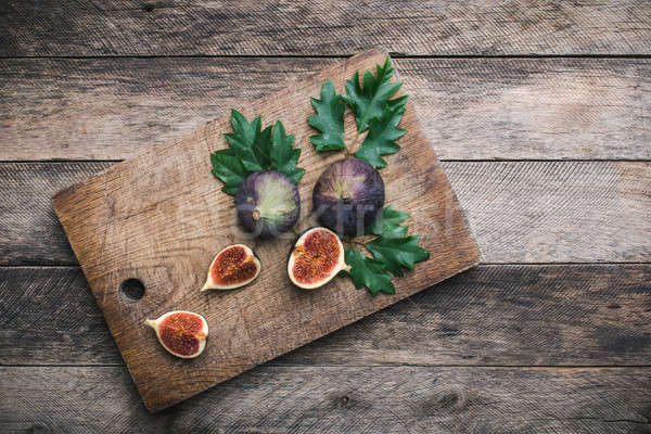 Cut Figs on chopping board and wood table Stock photo © Arsgera