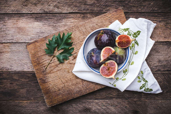 Figs in flat dish on choppingboard and napkin in rustic style Stock photo © Arsgera