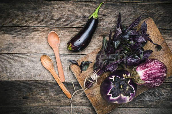 Aubergines with basil and two spoon on wood boards Stock photo © Arsgera