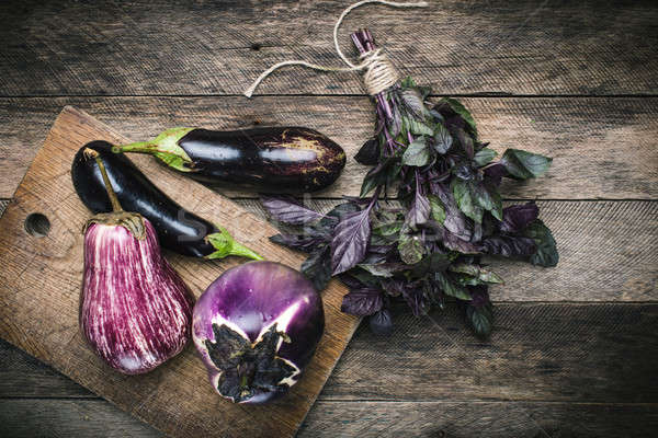 Aubergines and basil on chopping board and wooden table Stock photo © Arsgera