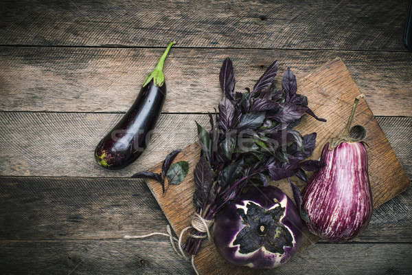 Aubergines and basil on chopping board  Stock photo © Arsgera