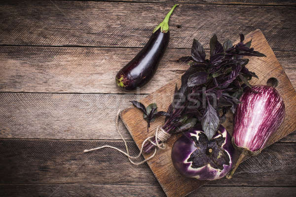 Tasty Aubergines and basil on chopping board and wooden table Stock photo © Arsgera
