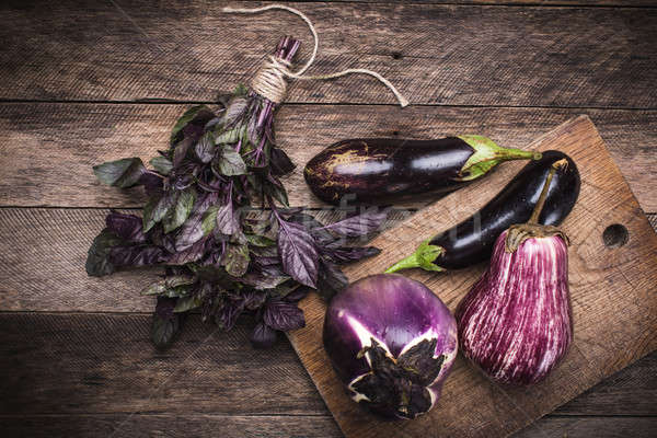 Aubergines and basil on chopping board in rustic style Stock photo © Arsgera