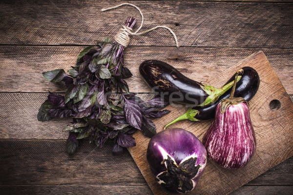 Rustic style Aubergines and basil on chopping board  Stock photo © Arsgera