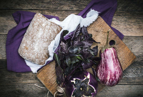 Aubergines basil and bread on chopping board Stock photo © Arsgera