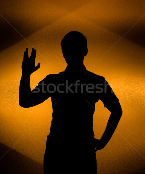 Back lit silhouette of man with raised hand Stock photo © Arsgera
