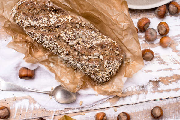 Bread with seeds huzelnuts on wooden board Stock photo © Arsgera