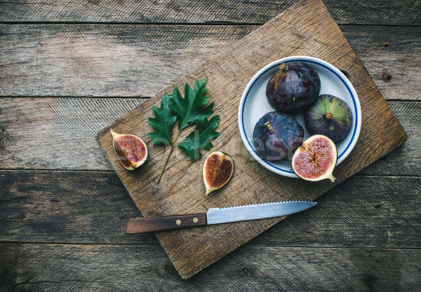 Cut Figs and knife on chopping board in rustic style Stock photo © Arsgera