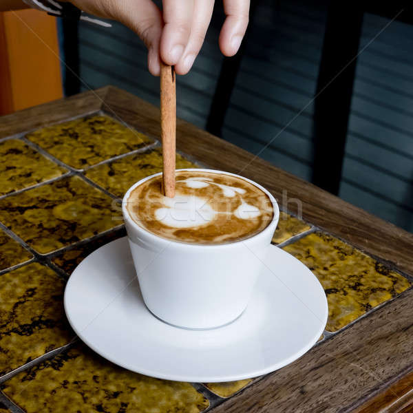 A coffee cup Latte being stirred by Cinnamon sticks. Stock photo © art9858
