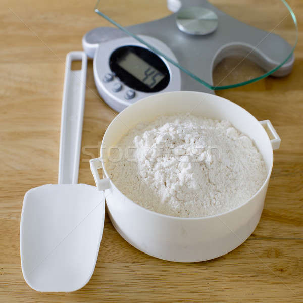 Bread flour in white bowl with rubber scraper and scale on wood  Stock photo © art9858