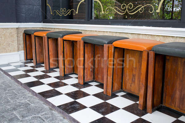 Classic wooden bar stools are lined up at an outdoor bar. Stock photo © art9858