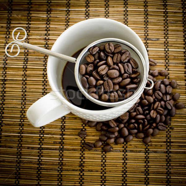 Xícara de café grão de café mesa de madeira beber copo quente Foto stock © art9858