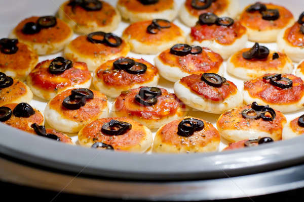 round meat pies with topping black olive sliced on buffet line Stock photo © art9858