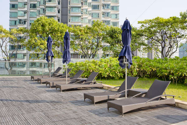 Wooden Pool beds and umbrella with daylight Stock photo © art9858