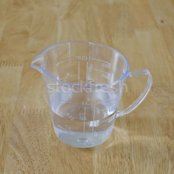 warm water in measuring cup on a wood background Stock photo © art9858