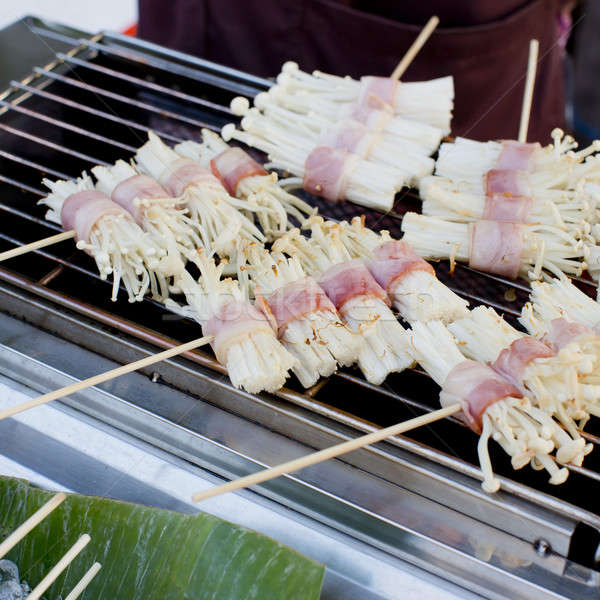 Roast bacon wrapped Flammulina Velutipes with skewer, street foo Stock photo © art9858