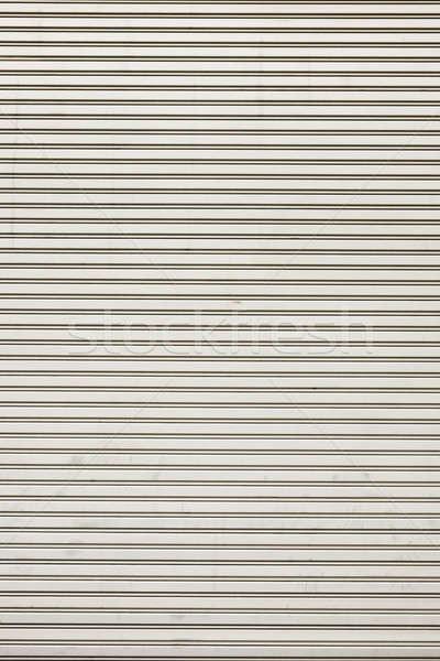 Steel shiny rolling shutter door texture with horizontal lines. Stock photo © art9858