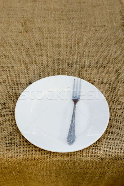 Place setting with plate and fork against brown plate mat Stock photo © art9858