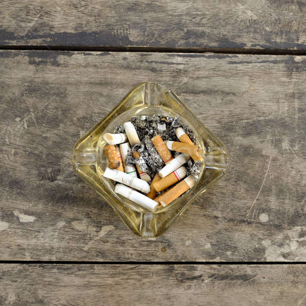 ashtray full of butt cigarettes on wooden background Stock photo © art9858