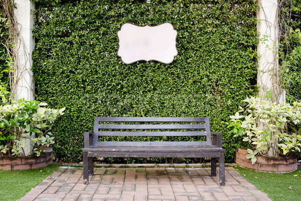 Wooden dark brown bench and blank vintage card against green lea Stock photo © art9858