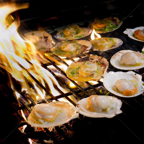 Grilled scallops topped with butter, garlic and parsley on flami Stock photo © art9858