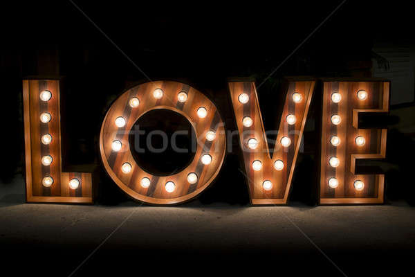 Wording Love sign with light bulb isolate on black background Stock photo © art9858