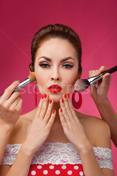 Woman with makeup brushes.   She is standing against a pink background. Stock photo © artfotodima