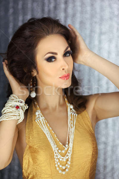 Beauty fashion model woman touching her curly and brown hair prepering for party Stock photo © artfotodima