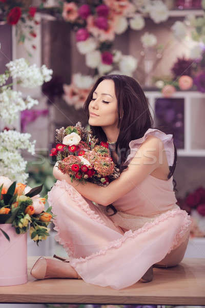 Beautiful asian woman florist in pink dress with bouquet of flowers in hands in flower store Stock photo © artfotodima