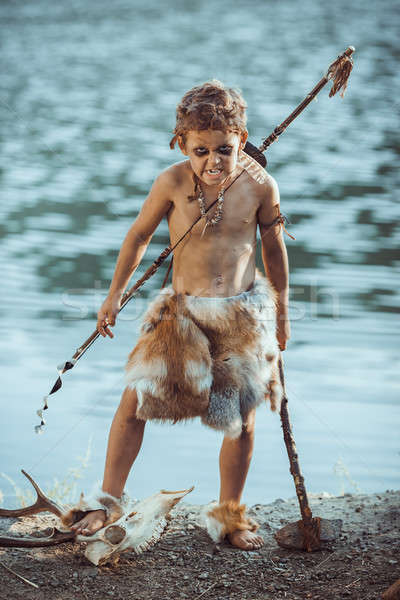 Angry caveman, manly boy with primitive weapon hunting outdoors. Ancient prehistoric warrior. Heroic Stock photo © artfotodima