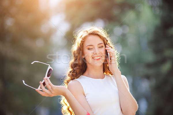 Mulher caminhada rua falante telefone elegante Foto stock © artfotodima