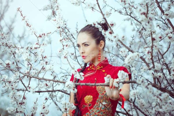 Geisha in red kimono in sakura Stock photo © artfotodima